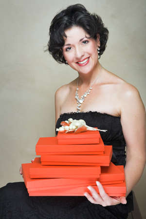 Beautiful woman in little black dress of lace, wearing pearls, sitting with red boxes piled on her lap, short curly hair photo