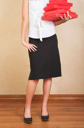 pencil skirt: Young businesswoman in white shirt and black pencil skirt holding red gifts boxes