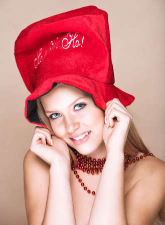 sweet seventeen: Blond teenage girl on beige background with red shiny necklace and Christmas hat with Ho! Ho! Ho!, laughing.