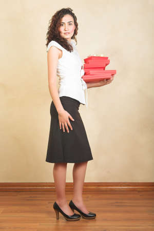 Young businesswoman in white shirt and black pencil skirt holding red gifts boxes  photo