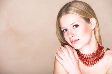 Blond teenage girl with loose straight hair on beige background with red shiny necklace and soft smile. Natural make-up Stock Photo - 2127762
