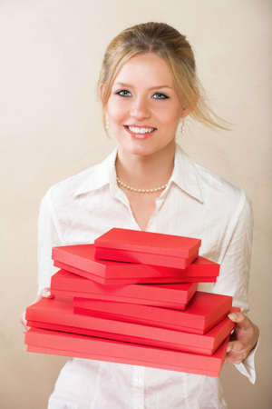 Blond businesswoman with blue eyes in white office shirt holding red gift boxes photo