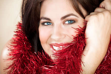 brown hair blue eyes: Beautiful woman with long brown hair, blue eyes and red tinsel Stock Photo