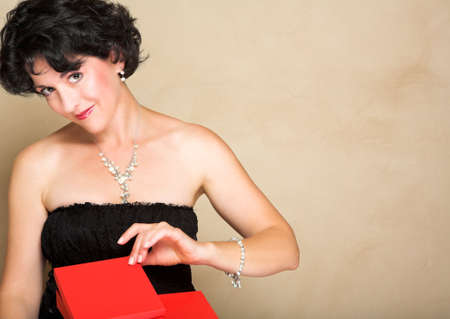 lbd: Woman in lace black dress with short curly hair, wearing pearls, opening a red gift box