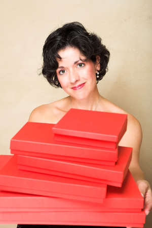 Smiling woman with short curly hair, holding a stack of red gift boxes Stock Photo - 2180156