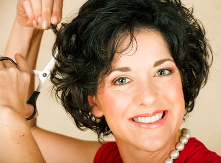 Beautiful happy adult woman  with black curly hair cutting her hair with scissors. Visible skin texture with pores and wrinkles Stock Photo