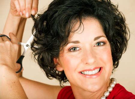 Hermosa mujer adulta feliz con el cabello negro rizado corte el cabello con tijeras. Visible con textura de la piel los poros y arrugas  Foto de archivo - 2354301