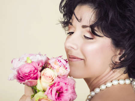 pores: Beautiful adult woman  with black curly hair holding pink spring flowers bouquet. Good visible skin texture with pores and fine wrinkles Stock Photo