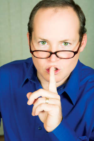 shutup: Man with green eyes in blue shirt wearing glasses  demanding silence with finger next to his mouth