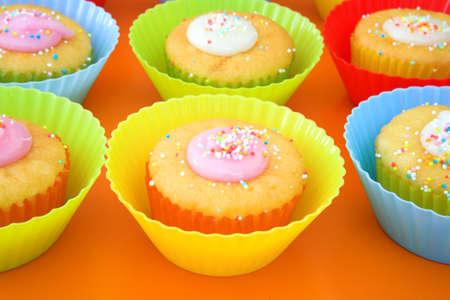 sucre glace: Affichage des petits g�teaux partie de sucre glace dans des tasses en plastique brillant. Focus sur le g�teau milieu