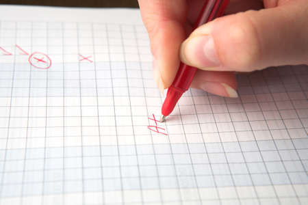 Woman teacher marking a test paper with an A+, holding a red pen, shallow depth of field with focus on the A. photo