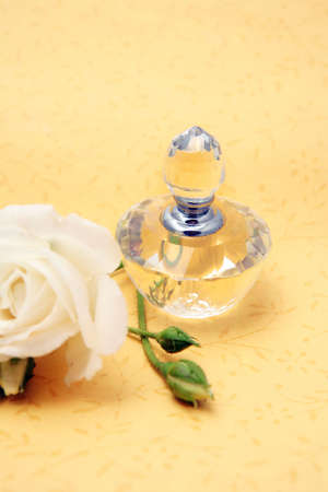Crystal perfume bottle on yellow background and a white rose photo