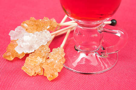 White and brown sugar sticks and herbal tea in glass mug on pink material background photo