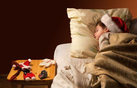 Little boy sleeping next to Santas uniform laying on a stool