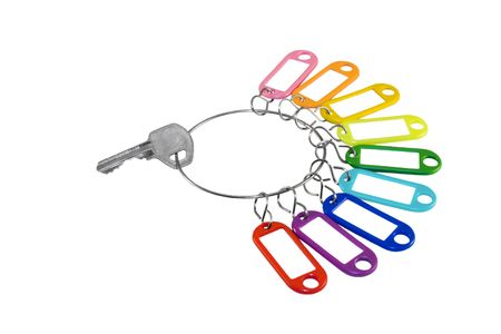 tinge: Stell key and multicolored plastic trinkets on a white background Stock Photo