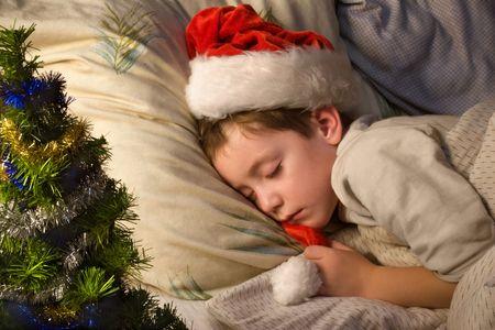 Little boy in Santas hat sleeping next to Cristmas tree