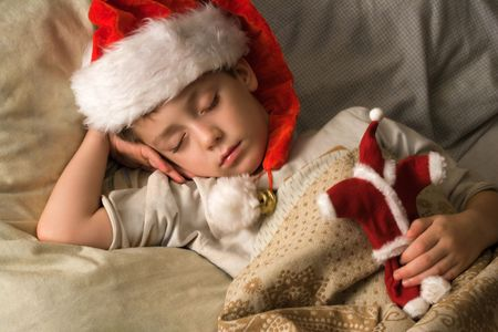 Little boy in Santas hat sleeping with a toy in a hand Stock Photo