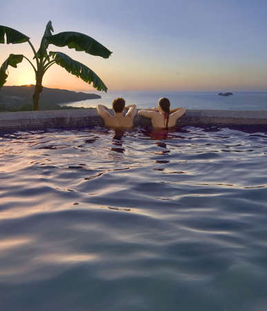 timeshare: Young couple watches the sunset from an oceanside pool in Costa Rica