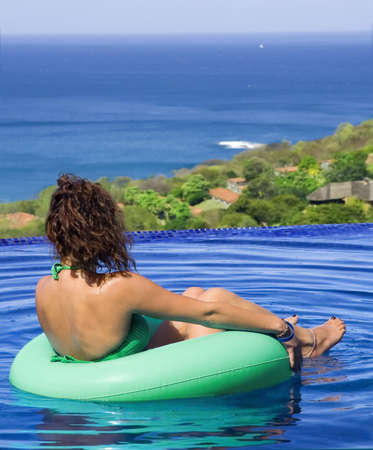 timeshare: Young woman relaxes in a pool near the ocean Stock Photo