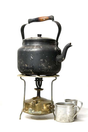 Isolated image old smoked teapot on a kerosene stove. Stock Photo