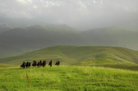herdsman: Kazakh herdsman (shepherd) drive horses at mountain pasture. Stock Photo