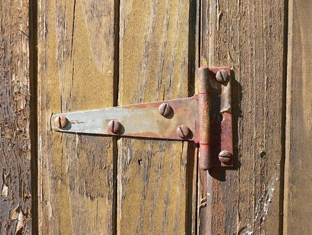 corrode: A rusty hinge on a weathered barn door.
