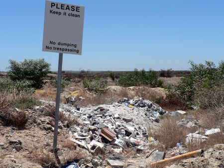eyesore: No dumping or trespassing sign next to a pile of garbage.