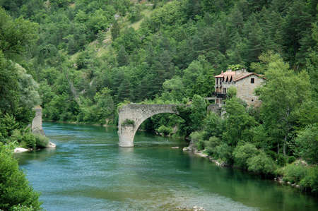 traditional house: Outside the city called Le Rozier, in the western part of the Tarn Gorges in France, a traditional house and a broken bridge can be found on the left bank of the river Tarn. Here the river is a frontier between the Midi-Pyrenees and and Languedoc-Roussill