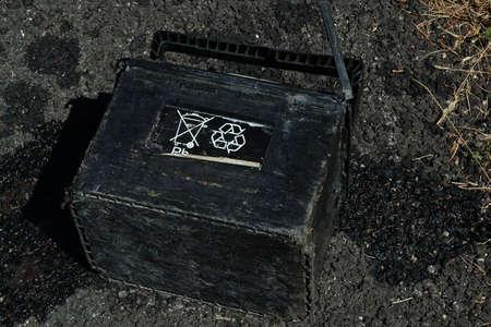 reciclable: Una bater�a de auto fugas de la izquierda en la carretera y que muestra el No arroje basuras en los s�mbolos y Reciclaje boca arriba. Horizontal cerca.