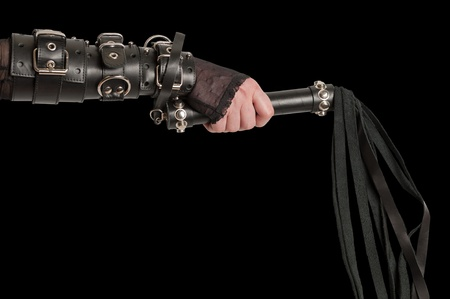 bdsm: Hand in Leather Cuffs with Lash on Black