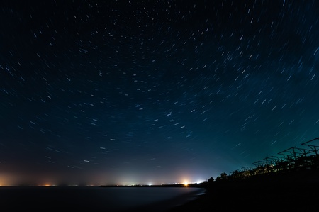 Night coast under star trails rounded photo