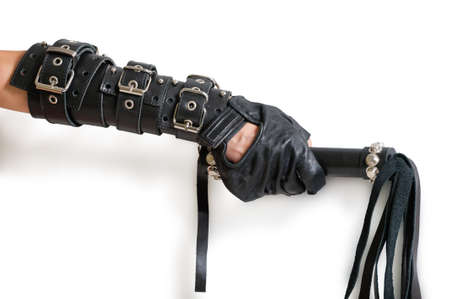 domination: Hand in leather glove with lash and shadow