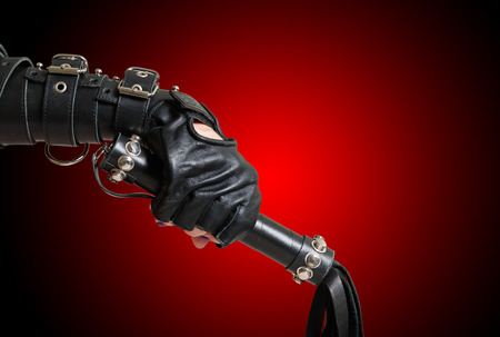 restraining device: Fist in leather glove with lash Stock Photo