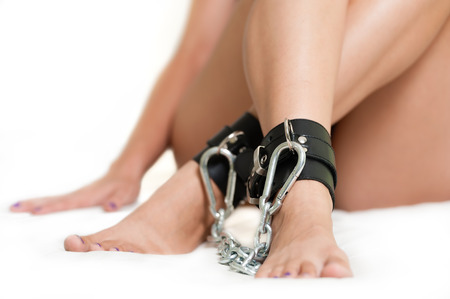 Legs in shackles on white photo