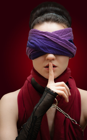 blindfolded: Blindfolded girl finger over lips red background