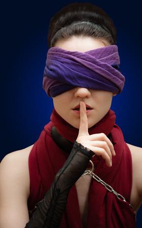 ojos vendados: Chica dedo ojos vendados sobre los labios Fondo azul