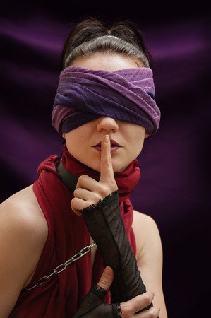 blindfolded: Blindfolded girl finger over lips violet blanket background Stock Photo