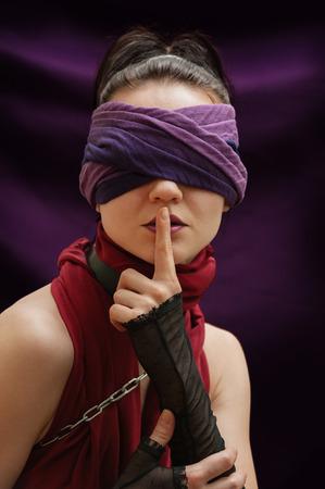 ojos vendados: Dedo chica ojos vendados sobre el fondo violeta labios manta Foto de archivo