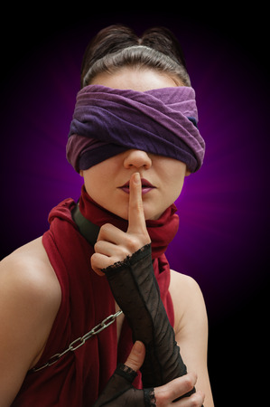 blindfolded: Blindfolded girl finger over lips violet background Stock Photo