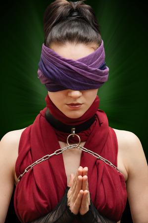 ojos vendados: Chica con los ojos vendados orar fondo verde Foto de archivo