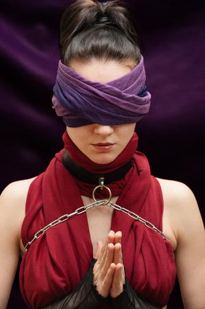 ojos vendados: Rezar con los ojos vendados chica fondo manta violeta Foto de archivo