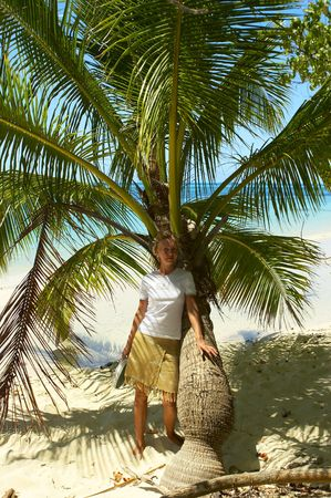 Woman under the palm tree on the island White Sands on Maldives Stock Photo - 428986