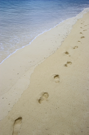 Fun footsteps on the coral sandy beach, Stock Photo