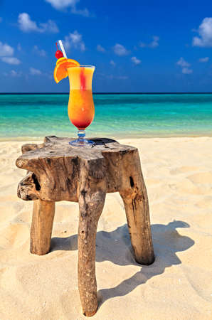 Glass of cocktail is on original  beach table is made from trunk of tree