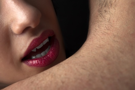Detail shot of vampiric female lips about to bit a mans neck Stock Photo