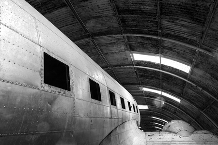 aileron: Abstract detail monochrome shot of a disused old aircraft in a hangar