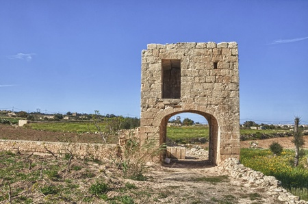 birthing: An elevated birthing chamber in the Maltese countryside, with an underlying arched underpass.