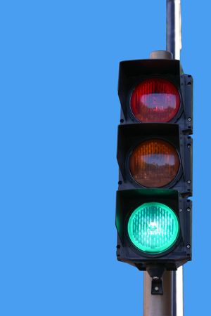 Traffic light showing green against blue background photo