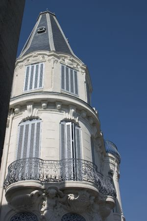 ironwork: Elegant balcony with lovely ironwork and pale blue shutters against a blue sky