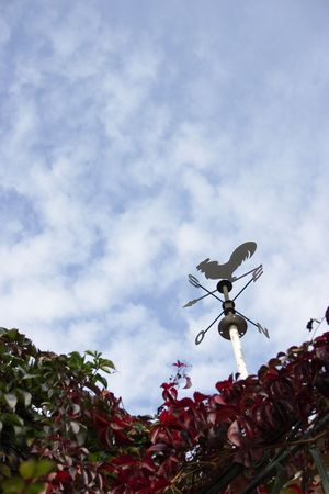 Nice metal weathervane against a cloudy but blue sky photo